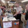 Geting ready: Gabe Boone signs his name to his deer license just after he bought it Friday evening at Trotter Sport Center in Sullivan. Bob Fish runs the cash register for his boss Joe Trotter, right.