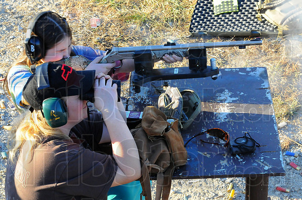 On target: Brittany Miller shoots her muzle loading rifle at the Minnehaha shooting range in Sullivan county Friday evening. Her mother Cherish watches through binoculars to see where her bullet hits. They along with Brittany's sister Elizabeth and dad Rob were preparing for the opening day of Deer gun season today.