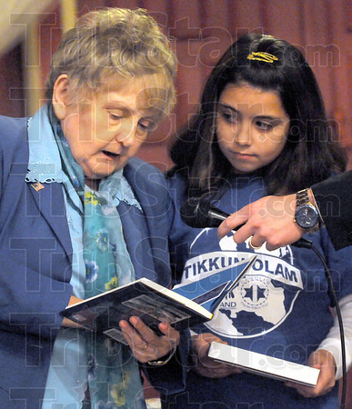 Winner: Ten-year-old Sierra Lowe listens as Eva Kor presents her with a copy of her book during a ceremony at the Indiana Theater Friday night. Sierra's card was one of several picked for distribution this year.