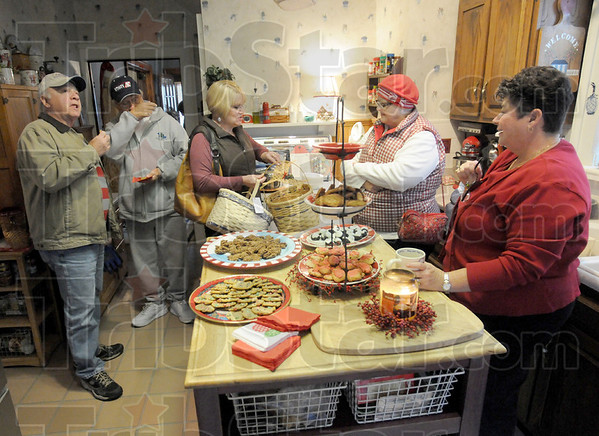 Tasty treats: Homeowner Arlene Jennings (R) welcomes Collett Park Christmas Walkers to her home on north 10th Street providing sugary treats for all visitors. They are (from left), brothers Larry and Gary Chavis of Brazil, Indiana, Penny Bluebaugh and Debbie Long.