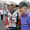 Community run: Mike Morris (L) introduces Joan Benoit-Samuelson to a gathering of runners prior to the start of the Community Run Saturday morning at Memorial Stadium. She is an Olympic Gold Medal winner for the women's marathon in 1984.