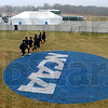 Getting to know you: A team of collegiate runners jogs down the straightaway past the NCAA logo Saturday afternoon.