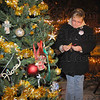 Remembering: Doreena Javins places an ornament on the Victims tre at teh candlelight vigil Saturday evening.