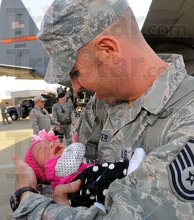 Daddy's home. MSgt. Jason Weyer of Ft. Branch Indiana holds his infant daughter Paige for the first time. He had just returned from a 7 month deployment to Saudi Arabia with the 181st Intelligence Wing security team.