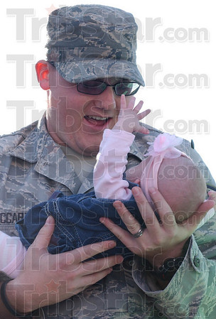 Love at first sight: Alan McCarter holds his daughter Addison for the fist time. He just arrived home with the rest of the 181st security team that had been deployed to Saudi Arabia for 7 months..