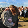 Welcome home: Indiana Air National guard Sergeant Alan McCarter gets a welcome home hug from his wife Stephanie while she holds their infant daughter. Six week old Addison was born while McCarter was deployed to Saudi Arabia with the 181st Intelligence Wing Security Forces Squadron.
