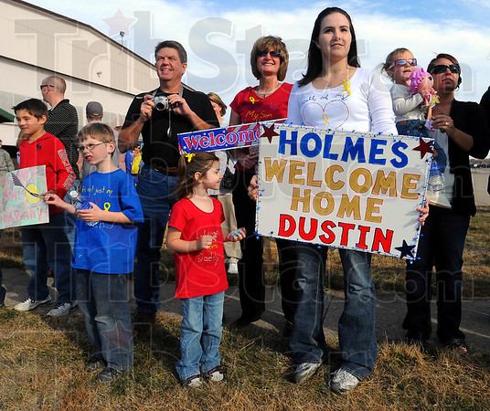 Watching and waiting: Jennifer Holmes holds a sign showing her feelings as she waits for her husband to return with the rest of the 181st Intelligence Wing Security Forces Squadron. With her are her children Tristan and Bella and her in-laws Gary and Susan Holmes.