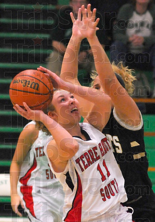 Up close: Kayla Ennen(11) finds tough going in the paint agaisnt the defense of South Vermillion's Kenzie Cheesewright.