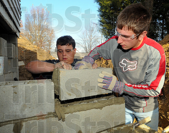 Teamwork: Dude Matherly and Scott Moody fit a block into place in the foundation wall.