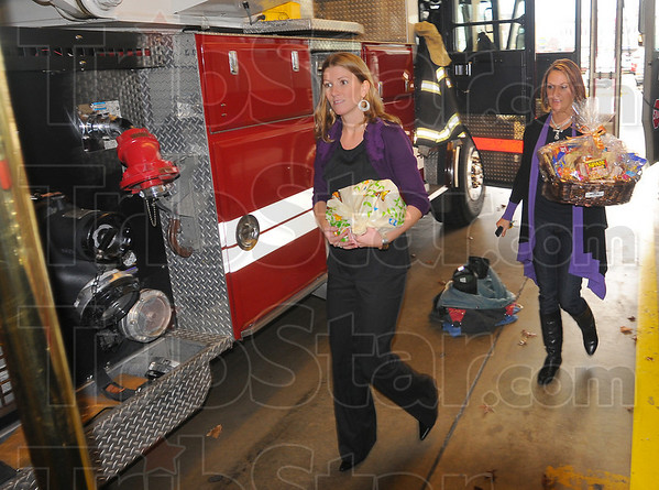 Gratitude: Jenny Strole and Natalie Overton of Servpro carry a thanksgiving basket into Terre Haute fire station #5 Monday afternon.