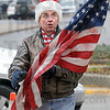 Patriotic chore: Rod Henry holds the Flag after it was lowered to the ground by a Duke Energy lineman that replaced it with holiday decorations along Wabash Avenue Tuesday afternoon.