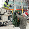 Santa's helper: Mayor Duke Bennett hands a holiday wreath to Win Energy employee Chad Jenkins Tuesday morning as crews install decorations along Wabash Avenue.
