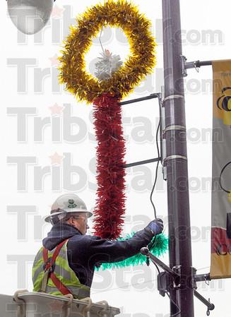 Install: Duke Energy employee Joe Hyrkas installs a holiday decoration on south 7th street Tuesday morning.
