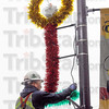 Install: Duke Energy employee Joe Hyrkas installs a holiday decoration on south 7th street Tuesday morning.