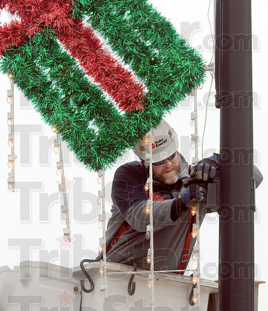 You light up my life: Duke Energy lineman Ryan Stultz installs a holiday decoration at the intersection of 9th and Wabash Tuesday afternoon.