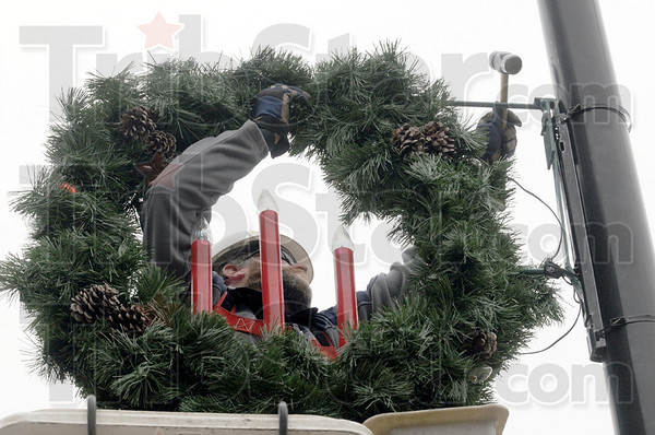 Hammer time: Duke Energy employee Ryan Stultz uses a bucket truck to install holiday decorations along Wabash Avenue Tuesday afternoon.