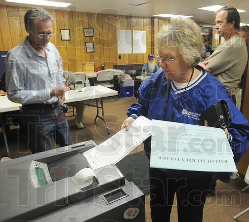 Make it count: Carolyn Miller feeds her completed ballot into the polling machine at the Collett Park pavillion Tuesday evening.