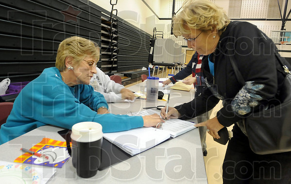 Sign here: Election clerk Lauralee Hawkins shows voter Nancy Knox where to sign before voting at Jackson Township school. Knox came straight to the school from her job substitute teaching in Cloverdale.