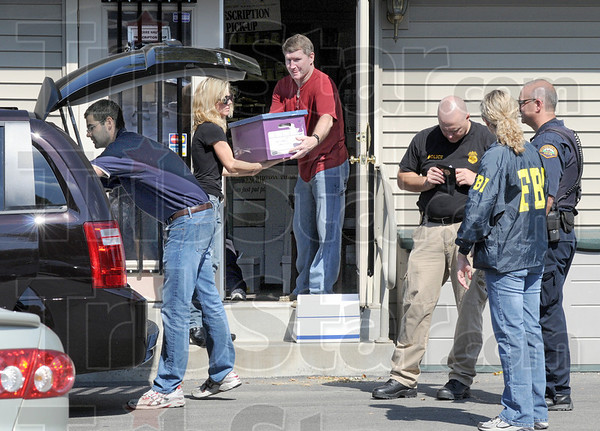Carry-out: FBI agents remove boxes of files from the Terre Haute Prescription Shop Thursday afternoon.