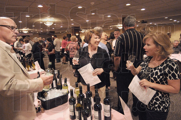 Tasty: Craig Hiatt waits for a response from Lacey Harden and Crystal Harris as the pair taste different wines at the fundraising event Thursday evening