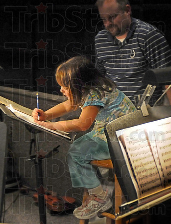 In the pits: Five-year-old Arianna Foster draws characters on a music stand in the orchestra pit at Terre Haute North Friday evening. Arianna's father Rodney Foster (standing) is directing the North orchestra during Friday's Harrison College Commencement event.