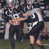 Handoff: Northview quarterback Trent Lancaster(10 hands the ball of to Damon Hyatt(30) in first quarter action of the Knights sectional semifinal game with Evansville Reitz.