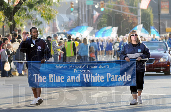 Let the parade begin: Two ISU students carryi the banner announcing the start of the annual Blue and White Parade.