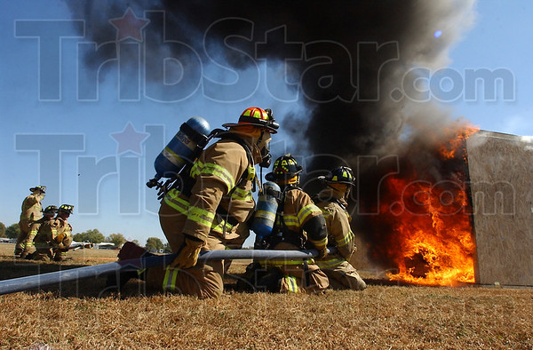 Fully involved: Honey Creek Fire Department firefighters wait for the word to extinguish the fire once it had flashed over at the home fire sprinkler demonstration Saturday afternoon at the Wabash Valley Fairgrounds.
