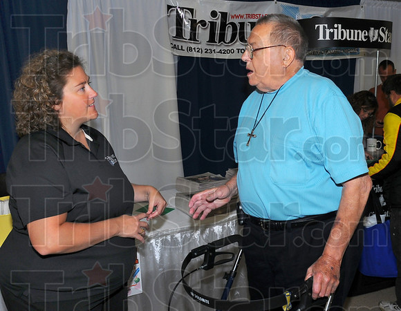 Catching up: Tribune-Star Marketing Director Courtney Zellars chats with former T-S employee Victor Saberton at the newspapers' booth at the Senior Expo 2010. The publication sponsored the event which hosted over 20 vendors.