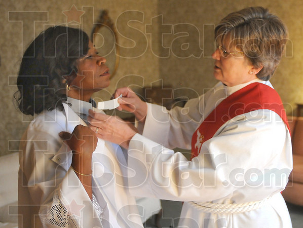 Learning curve: Fatima Madus gets a little help with her clerical collar from Reverend Deby Veach as they get ready for Madus' ordination ceremony at St. Stephen's Episcopal Church.