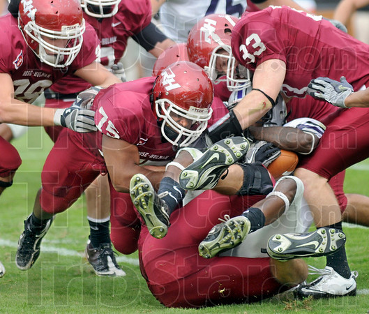 Grinder: A Bluffton ball carrier is disappears in the sea of red jerseys led by #75, Marcus Tucker and #33, Matt Green during Saturday's game.