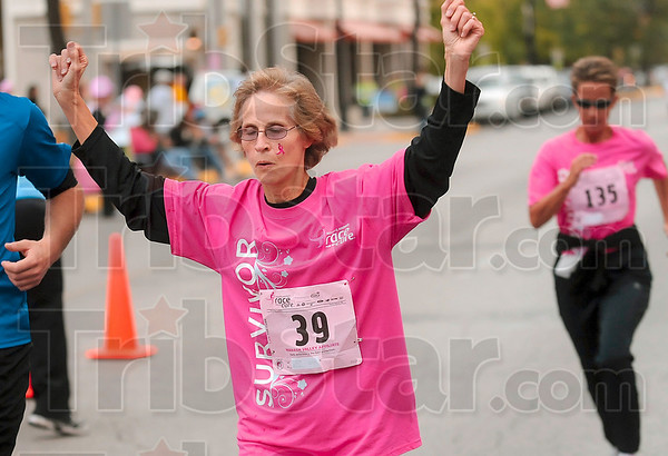 Tribune-Star/Joseph C. Garza<br /> The finish: 18-year survivor Pat Waters of Paris, Ill., triumphantly crosses the Race for the Cure finish line Saturday on Wabash Avenue. Waters ran with her son, Chris Waters.