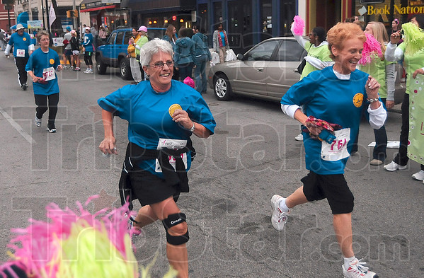 Tribune-Star/Joseph C. Garza<br /> In the race: Therese Gropp and Sue Cass of the Wabash Valley Road Runners spring to the finish line of the Race for the Cure Saturday on Wabash Avenue.