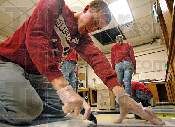 Can you cut it?: Haaken Hagen-Atwell cuts floor tiles for installation in the John Paul II High School Kitchen Saturday afternoon. Rose-Hulman students are volunteering their time during the Day of Service event.