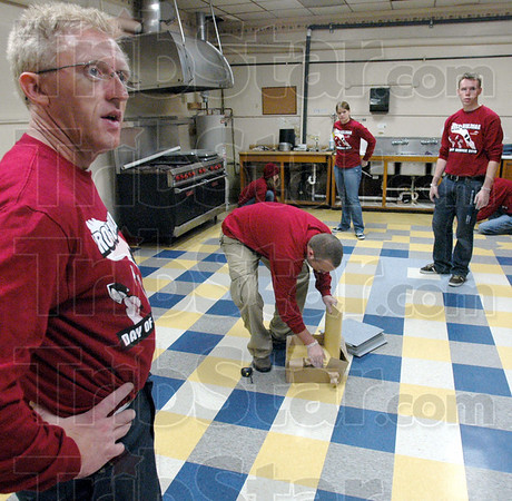 Ramrod: Rose-Hulman employee Charles Walls (L) works with Rose students as they install a new tile kitchen floor at John Paul II Catholic High School Saturday.