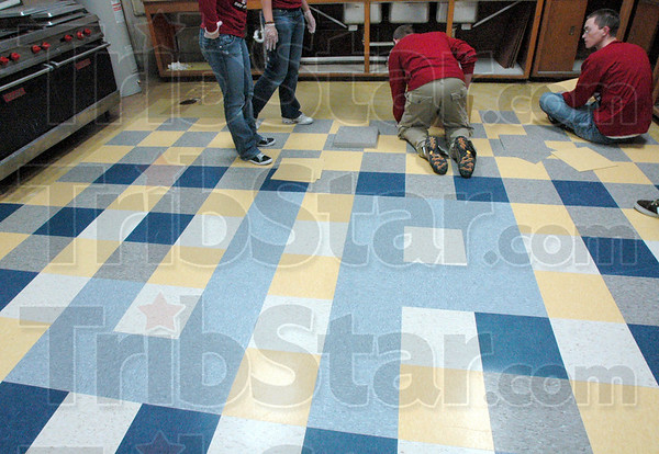 J.P.: Rose-Hulman students install tiles in the kitchen of the John Paul II High School Saturday morning. The initials J.P.  are visible in the floor pattern.