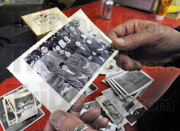 Family: Tim Popoff looks at photographs of his family Wednesday afternoon in his eastside business, Popoff Cleaners.