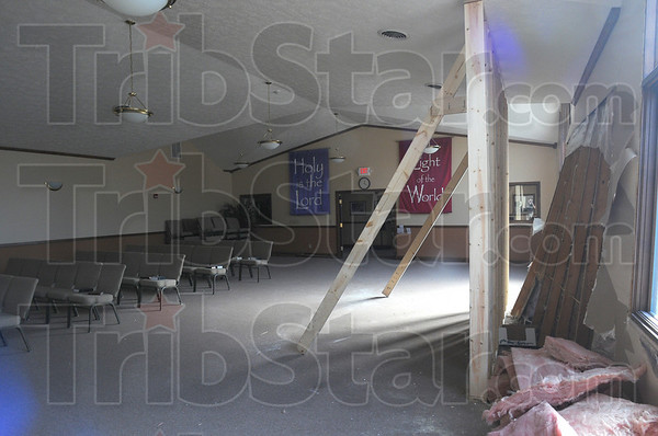 Altered altar: The interior of the Salvation Army chapel shows the violence of a week end accident where a vehicle crashed into the South 8th street structure. 2x6 support beams reinforce the ceiling in two places and drywall and insulation lay on the floor.