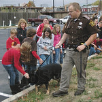 Good Doggy: Clay County Sheriff's Deputy Brian Swearingen leads K-9 partner Dayk to meet Staunton Elementary fifth-graders prior to a canine demonstration Monday outside the Clay County Just ...