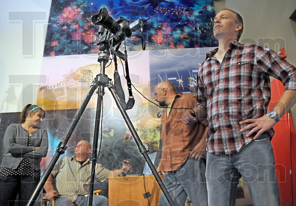 Picture this: Photographer John Bragg waits for the right moment to trip the shutter of his tripod mounted camera at the Terre Haute Children's Museum Monday morning. Productio team members Julie Boyle, Jeff Jeffrie and David Cordell discuss the images being transported to a computer during the shoot.