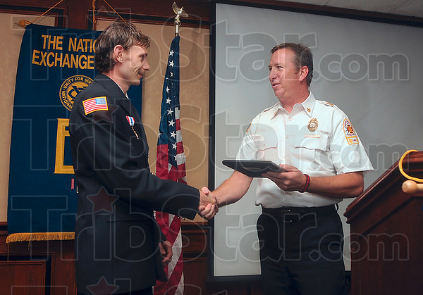 """Tribune-Star/Joseph C. Garza<br /> Saved the life of a little one: Terre Haute Firefighter William """"Billy"""" Roberts accepts the Exchange Club of Terre Haute's Fire Service Person of the Year award from Terre Haute Fire Chief Jeff Fisher Tuesday at the Holiday Inn."""