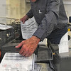 Paperwork: Election technician Don Smock feeds test ballots into a voting machine during a test of election day equipment.
