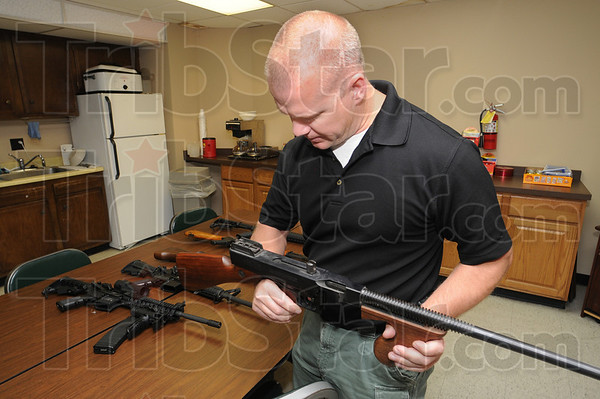 Top cop: Terre Haute police department detective Charlie Burress was honored by the Exchange Club of Terre Haute as Law Enforcement Officer of the Year. Here he looks for a manufacture date on one of a dozen or so guns seized in an ongoing investigation.