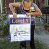 Install: Shelly Rector puts her yard sign in front of her Munchkin Land daycare and preschool business Tuesday morning.