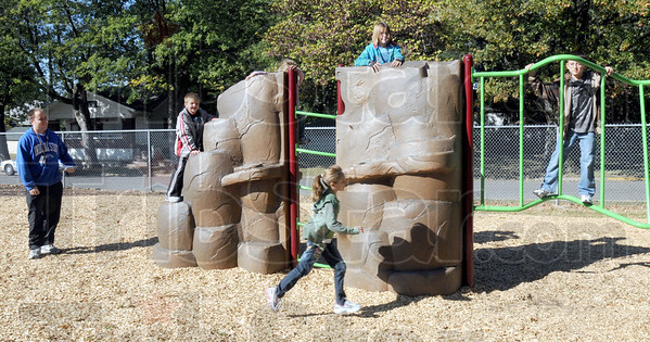 Exercise: Chris Conley (L) watches a group of Deming Elementary School kids playing on the new playground equipment at the school Tuesday morning. The school will receive a $16,000 check from GE Aviation to build a new track and exercise stations for the school.