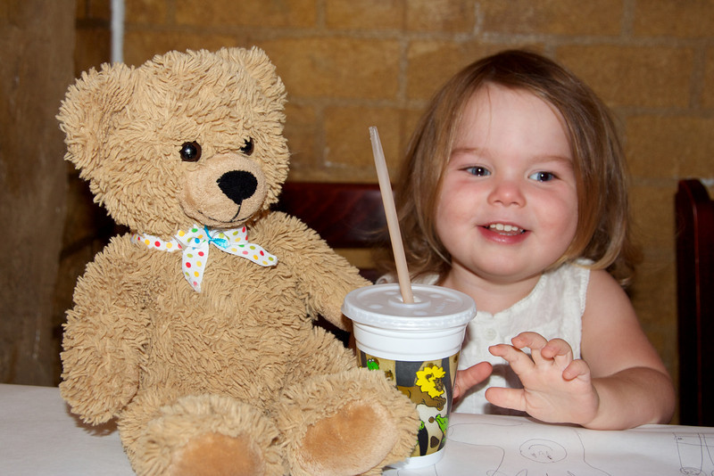 """Bizzy Bear goes to Mason's for Sunday brunch.  Anna is """"sharing"""" her very yummy chocolate milk, after much coaxing."""