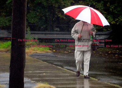 10/6/2010 Mike Orazzi | Staff A woman walks along Route 6 in Terryville during Wednesday's rain.