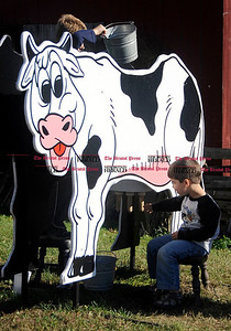 10/2/2010 Mike Orazzi | Staff Ethan Halstead,3, Farmington, milks a cow while at Minor's Farm during Family Farms Day on Saturday.