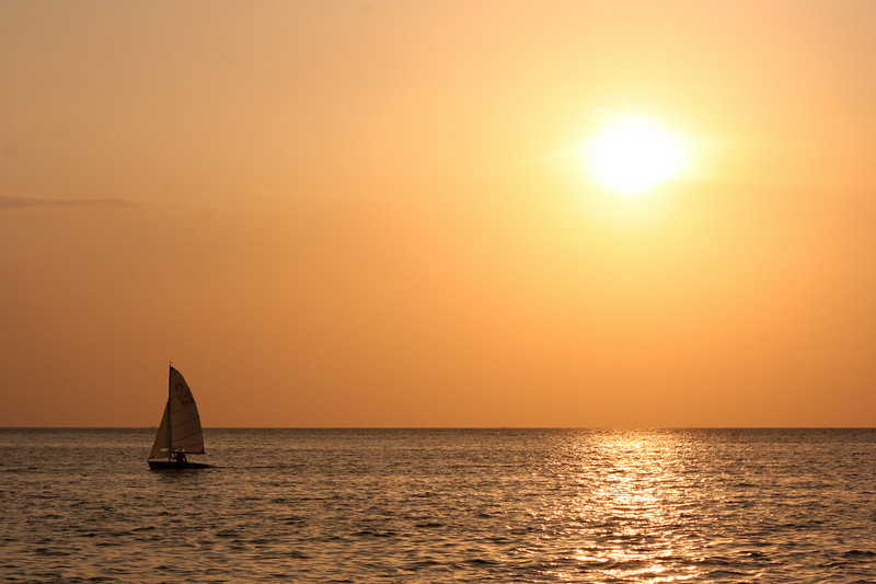 A late January sun catches a sailboat returning to port in the last moments of the day.
