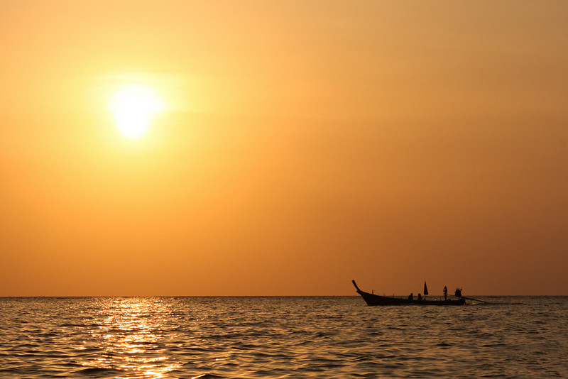 Sunset outlines a longtail boat carrying crew and passengers back to land.
